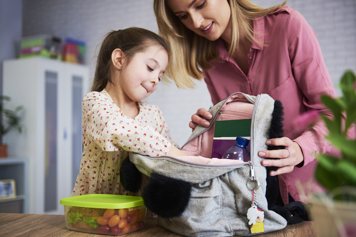 Ребенок собирает школьный рюкзак